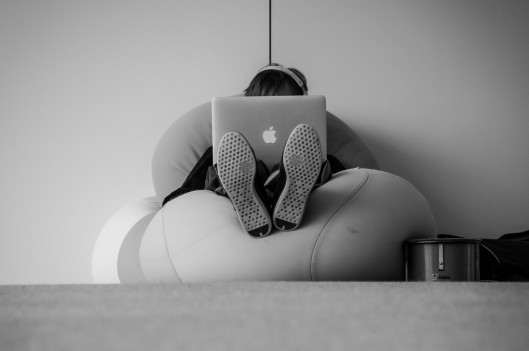 Man sitting alone with computer covering his face