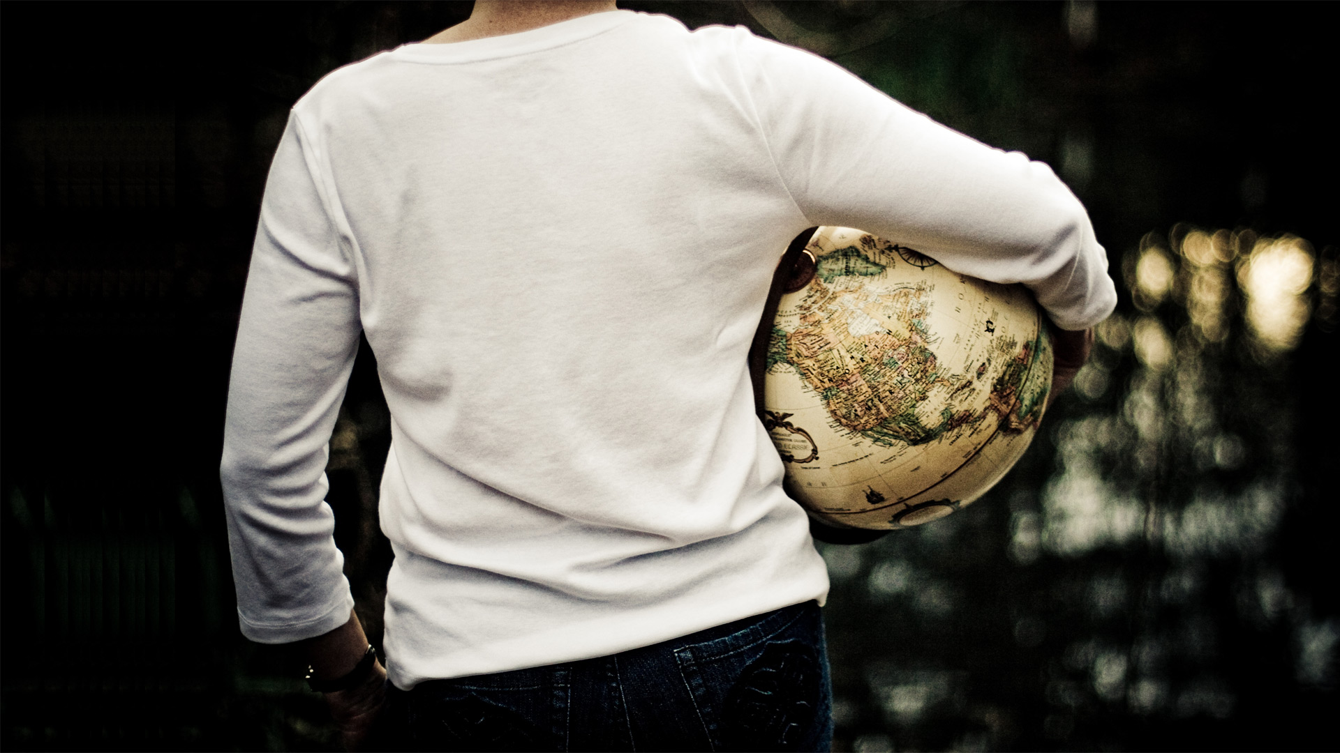 back view of woman holding a globe