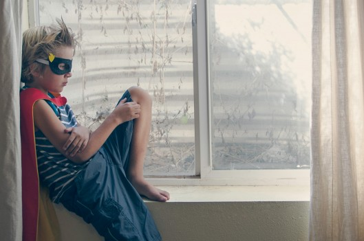 boy in superhero costume sitting on window ledge