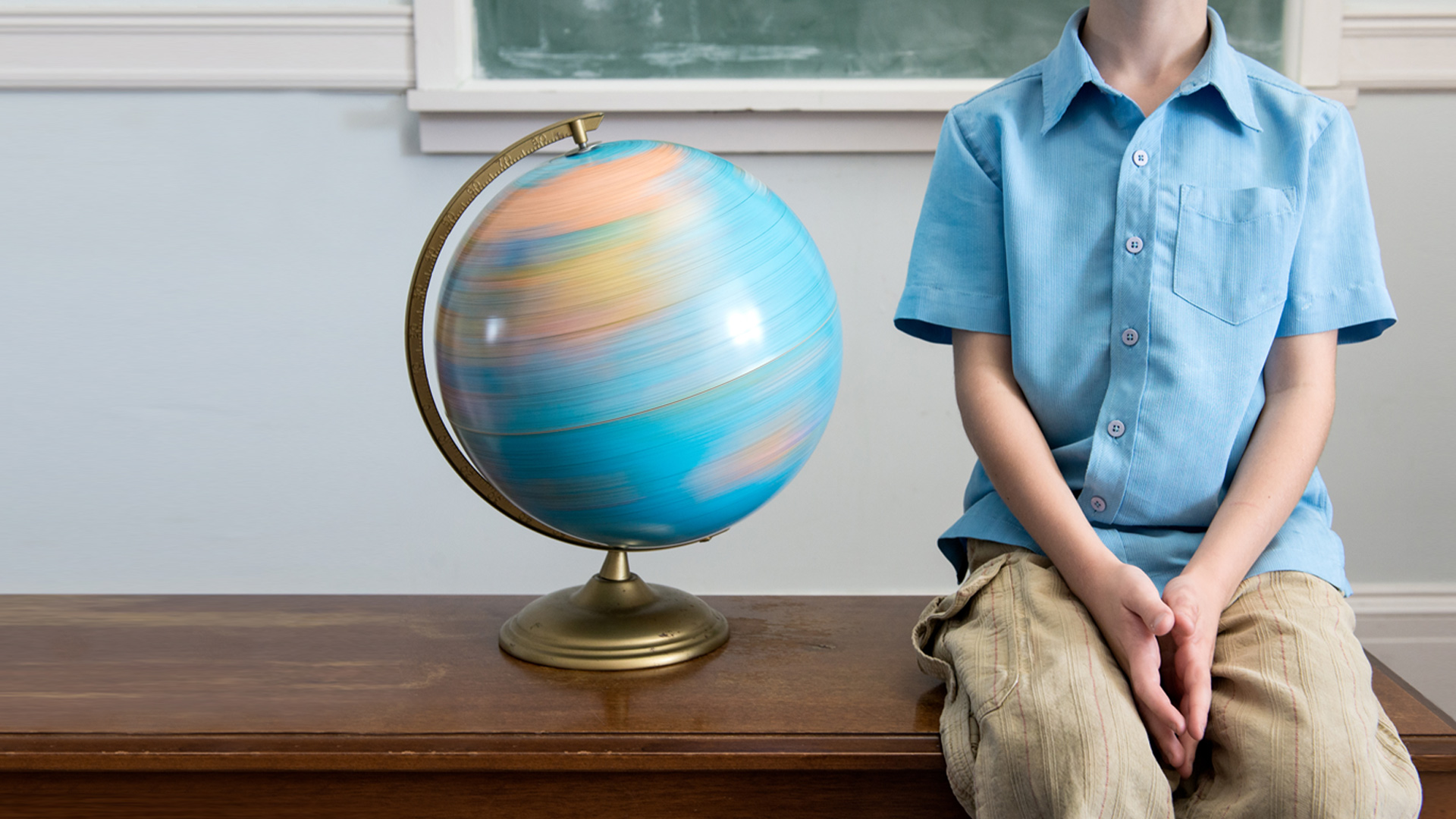 Child sitting on the teacher's desk