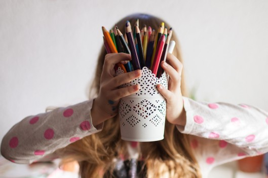 Girl holding colored pencils infront of her face
