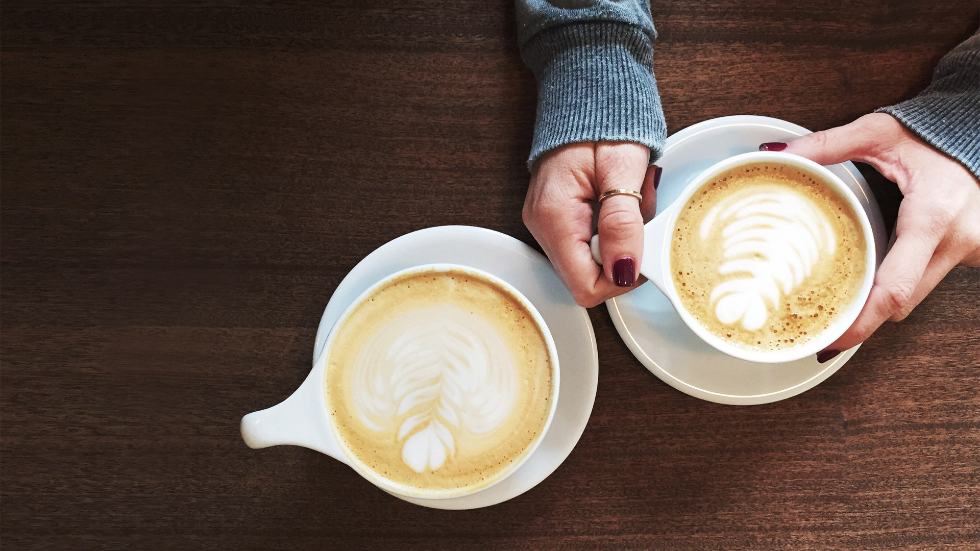 one woman's hands and two coffee cups