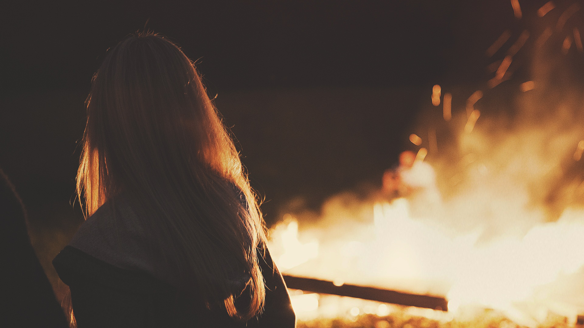 girl looking at the campfire