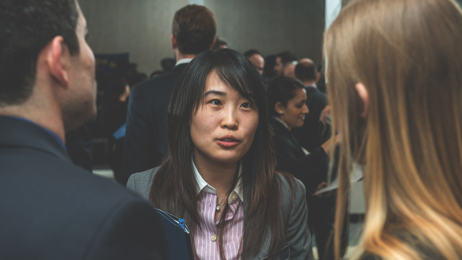 woman soeaking to two people at networking event