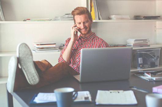 Man sitting at desk   Want to be Happy at Work? Care Less About It