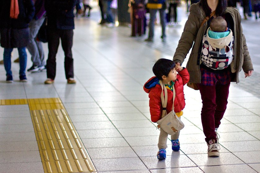 Little boy in red jacket holding his mother's hand