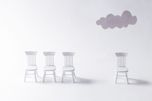 one chair separated from group of chairs with grey cloud over it