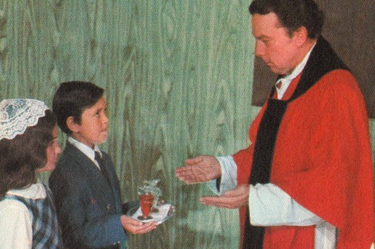 Priest giving children communion   Growing Up As a Reluctant Catholic