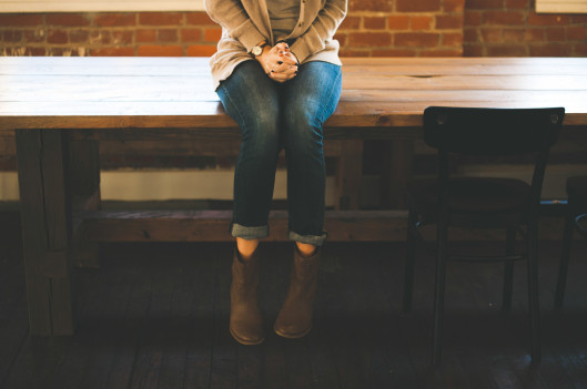 Woman sitting on table clasping her hands | On Being Introverted and Asian