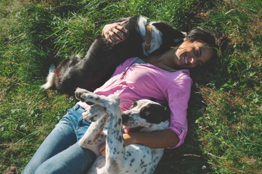 Woman Playing with Dogs in Grass | What We're Reading: The Importance of Play