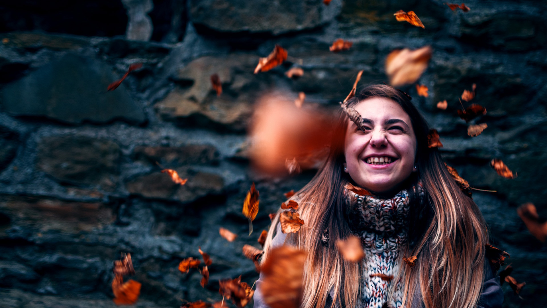 smiling girl with leaves in the air