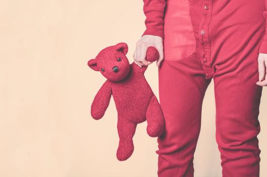 woman in onesie holding teddy bear