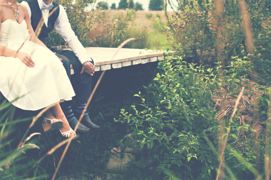 couple sitting on a deck on their wedding day