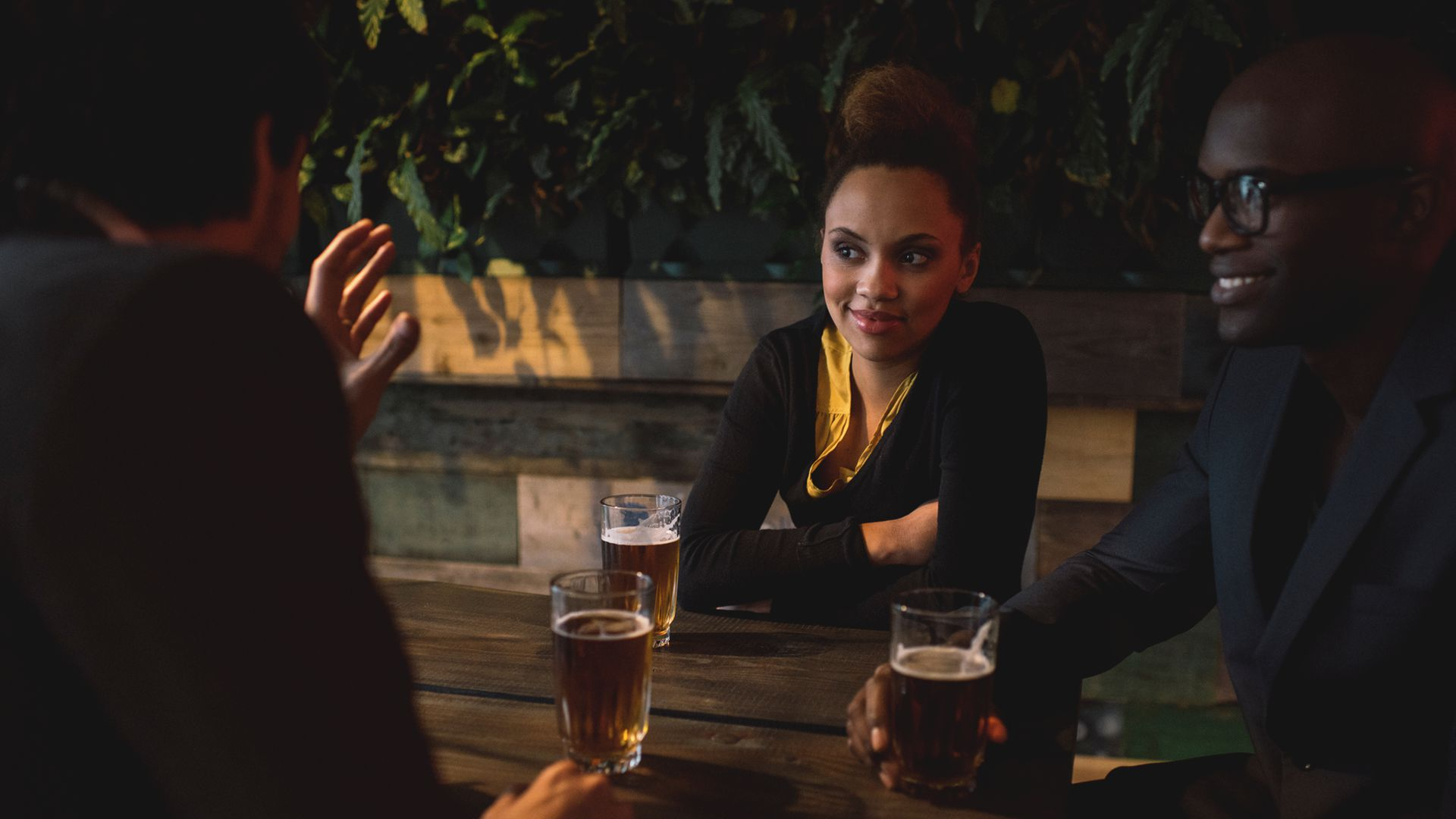 Three professionals around a table discussing something over drinks -- 4 Low-Risk Strategies for Expanding Your Network