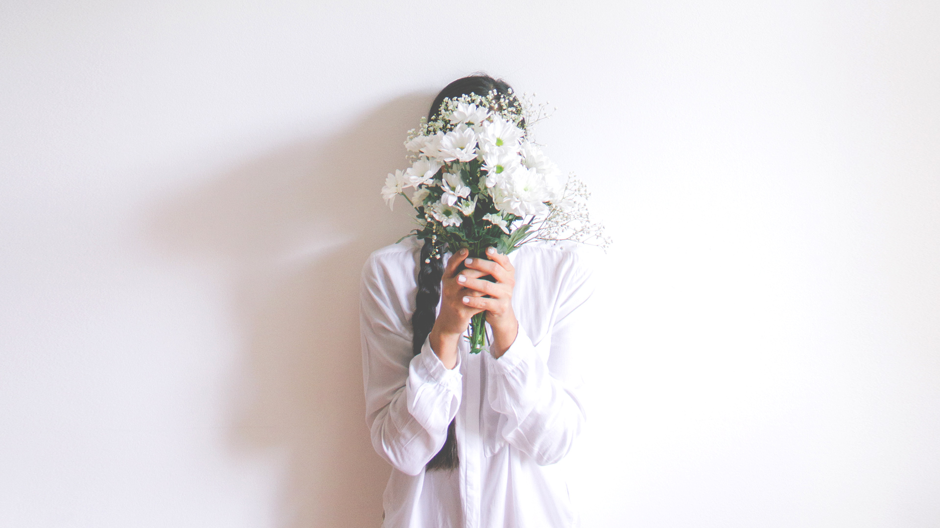 woman hiding behind bouquet of flowers