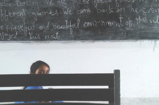 Shy girl in classroom hiding behind a chair