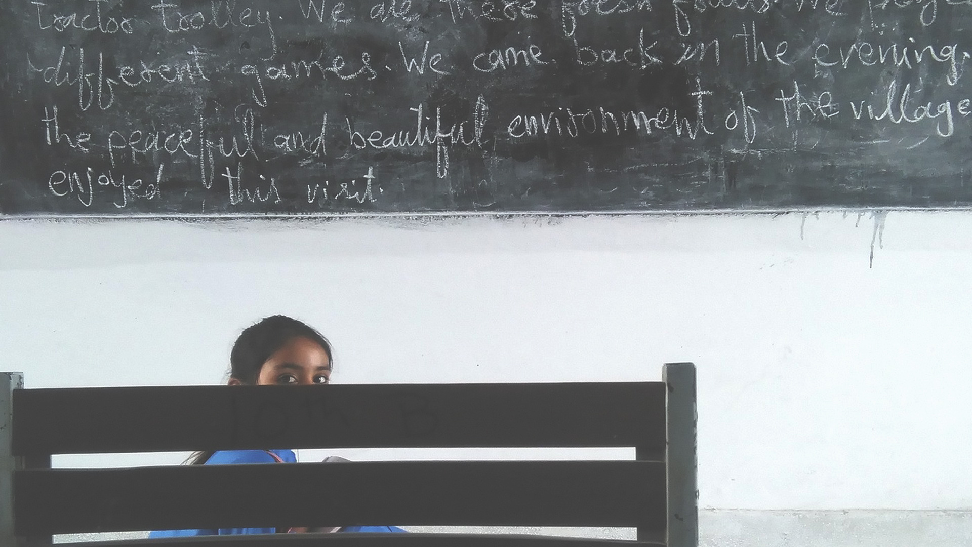Shy girl in classroom hiding behind a chair