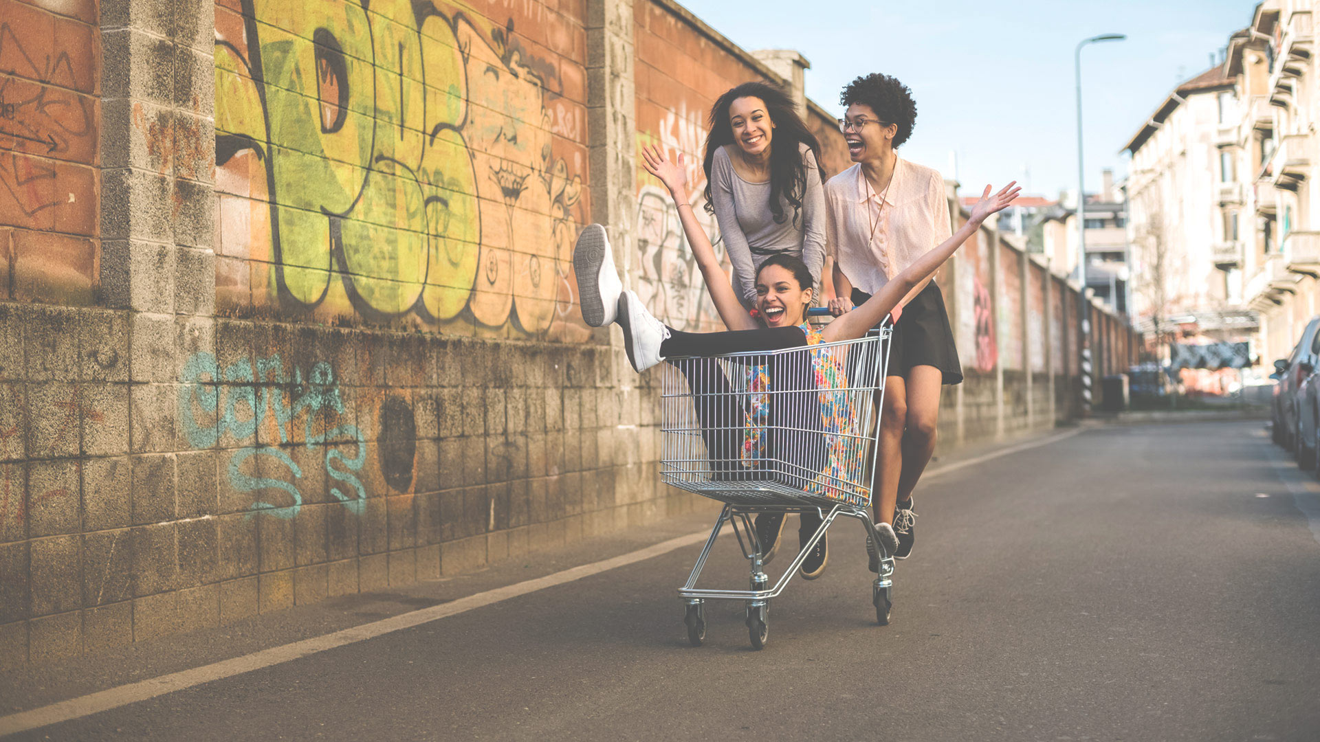 Group of friends having fun with a shopping cart