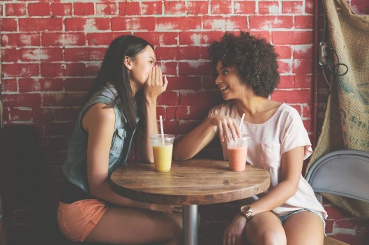 Two friends talking at a coffee shop