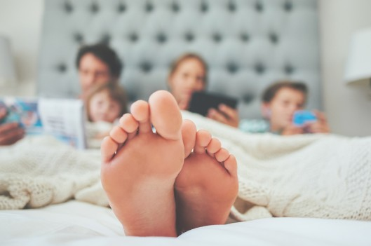 Family of four laying on a bed