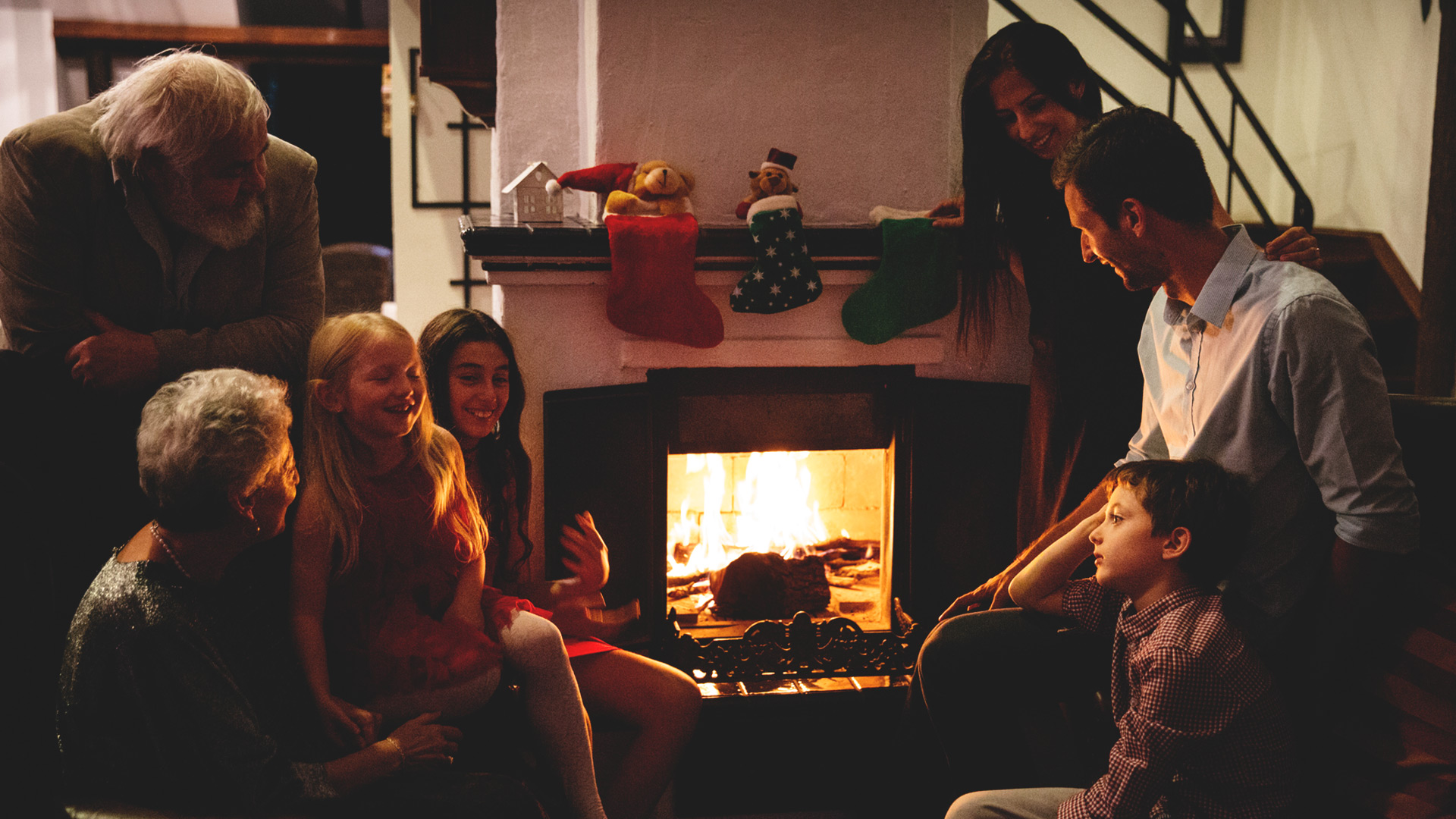 Family gathered at the fireplace at Christmas time