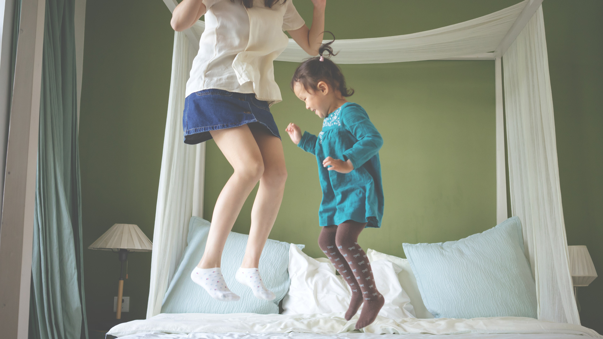 Mother and daughter jumping on the bed