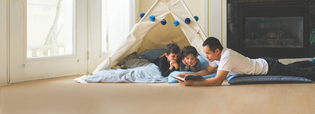 Father reading to kids in tent in house during daytime