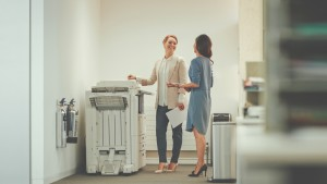 Two women interacting by the copy machine
