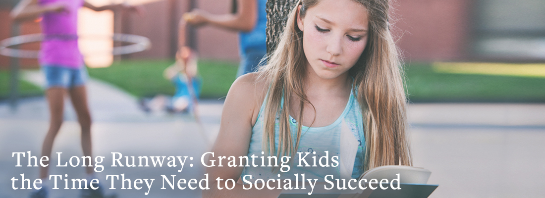 Girl reading alone while other children play together in the background | The Long Runway: Granting Kids the Time They Need to Socially Succeed