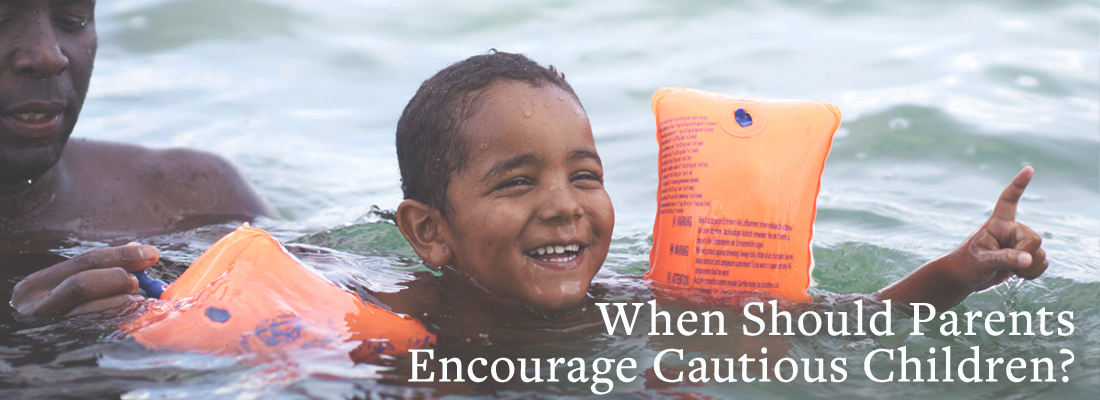 Young boy swimming | When Should Parents Encourage Cautious Children?