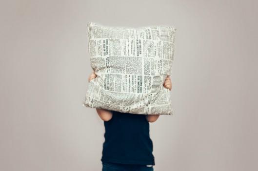 child hiding behind a pillow