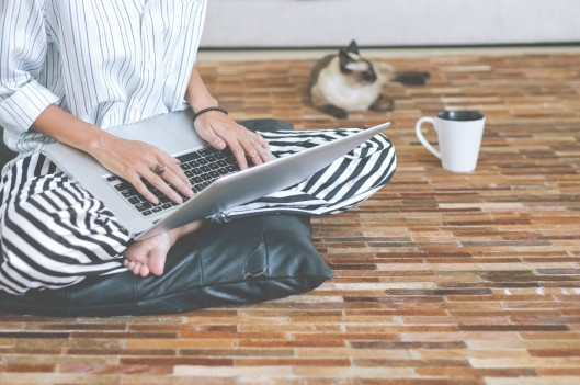 Woman working on her laptop on the floor