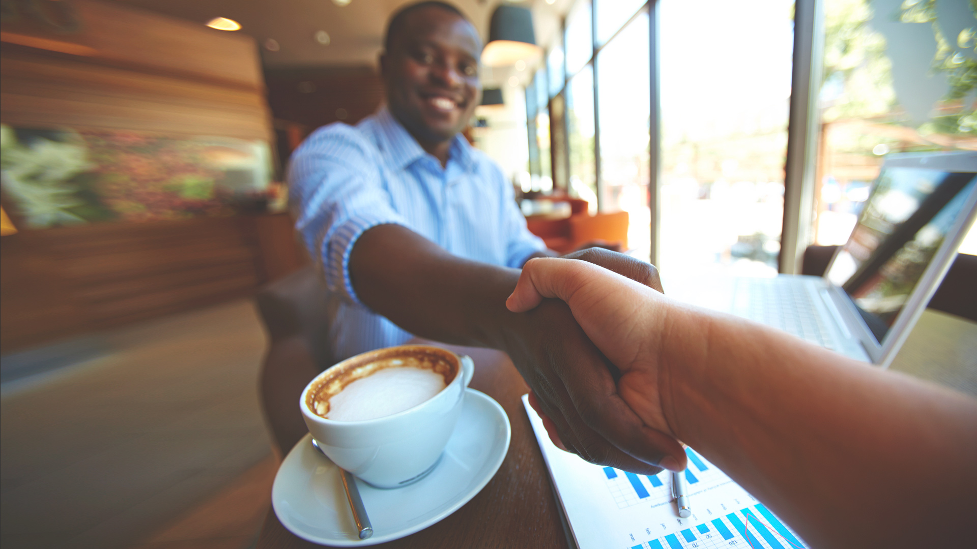 Man shaking hand while drinking coffee