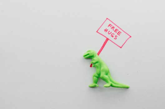toy t-rex with free hugs sign