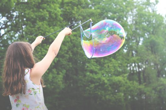 Young girl making a giant bubble