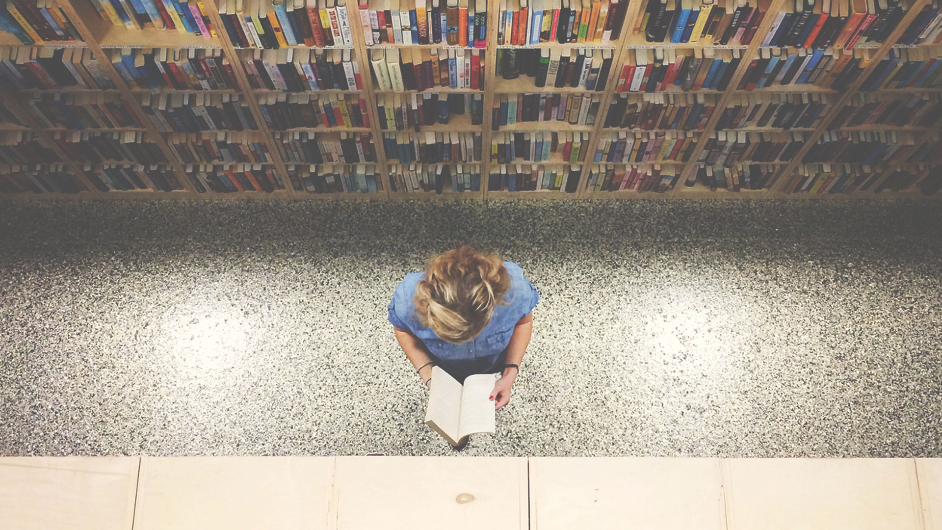 Woman reading book in college library
