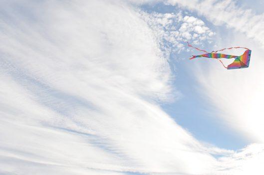 Kite flying through a sunny but cloudy sky