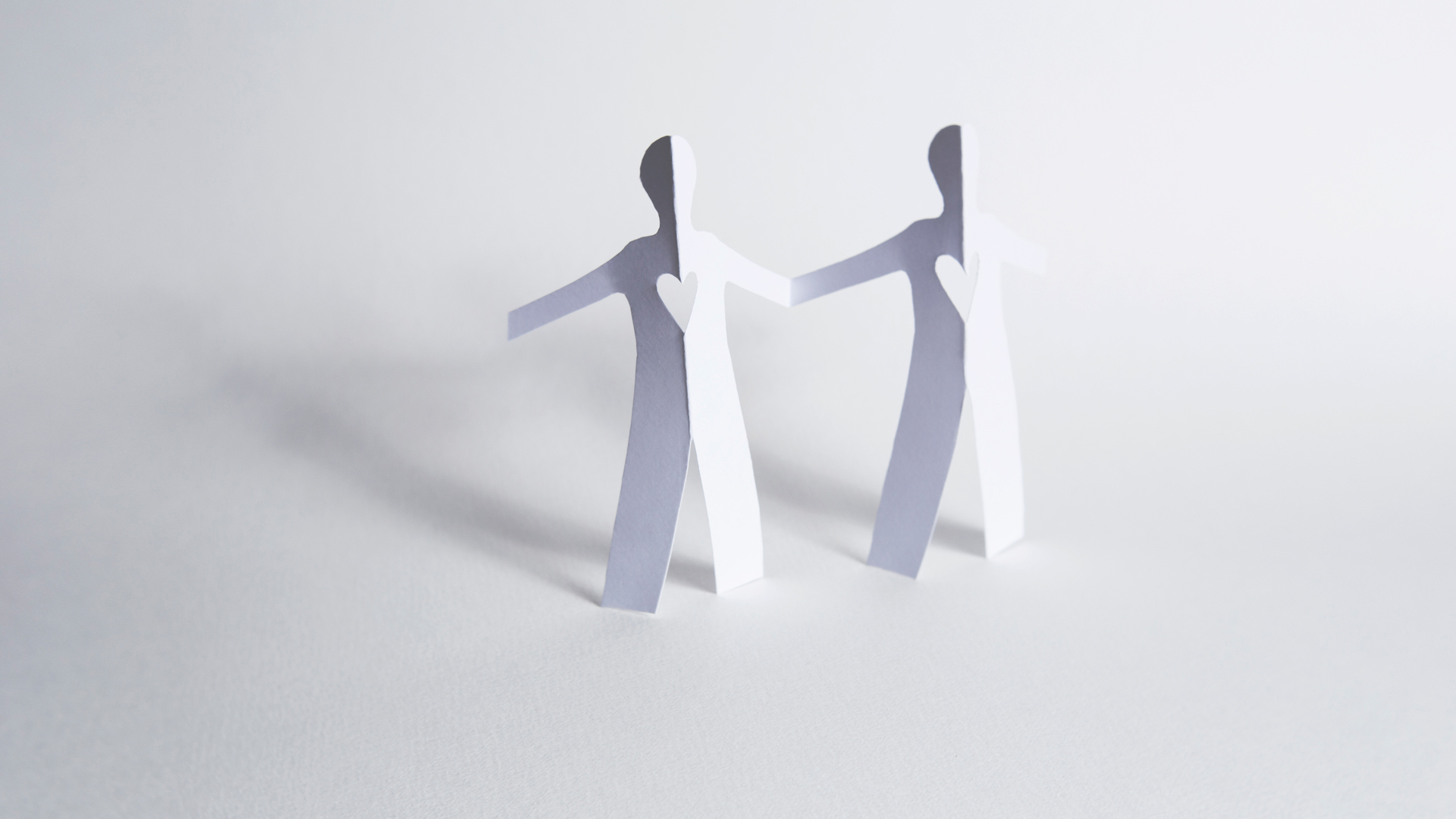 Paper cut out figures holding hands