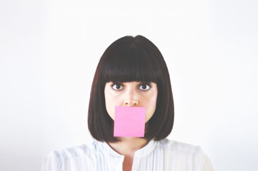 Woman with post-it covering her mouth