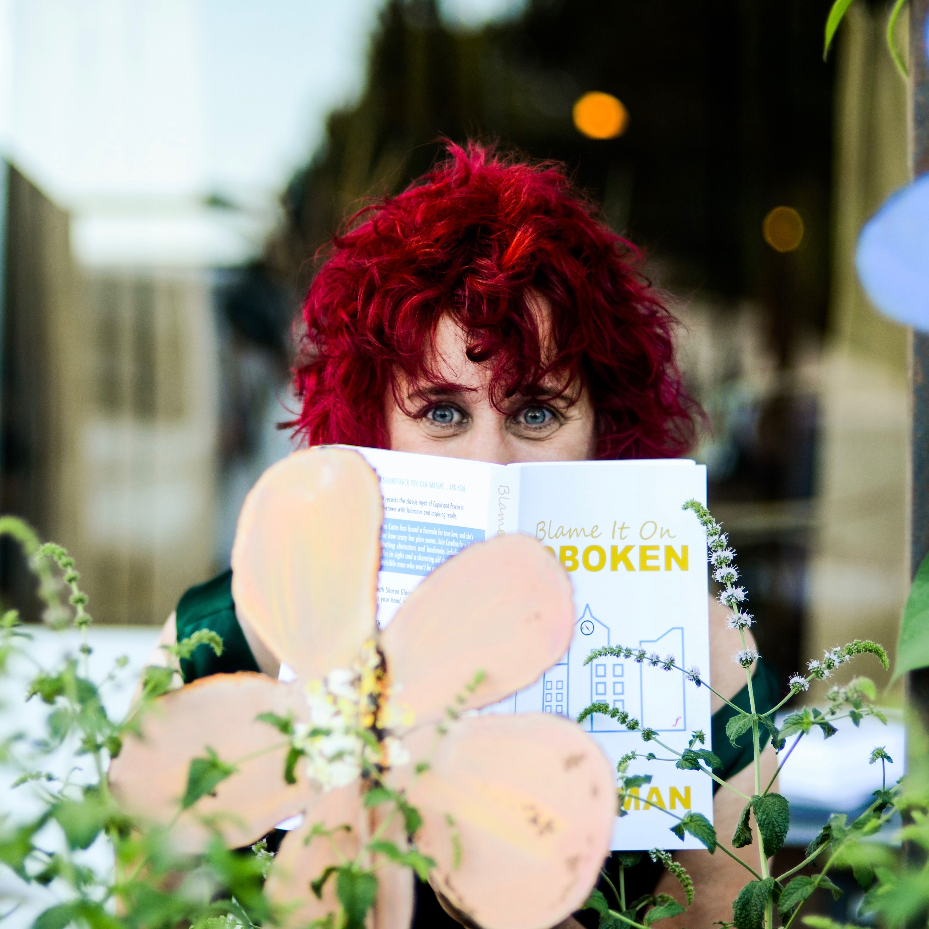 Sharon Glassman author photo with flowers and book