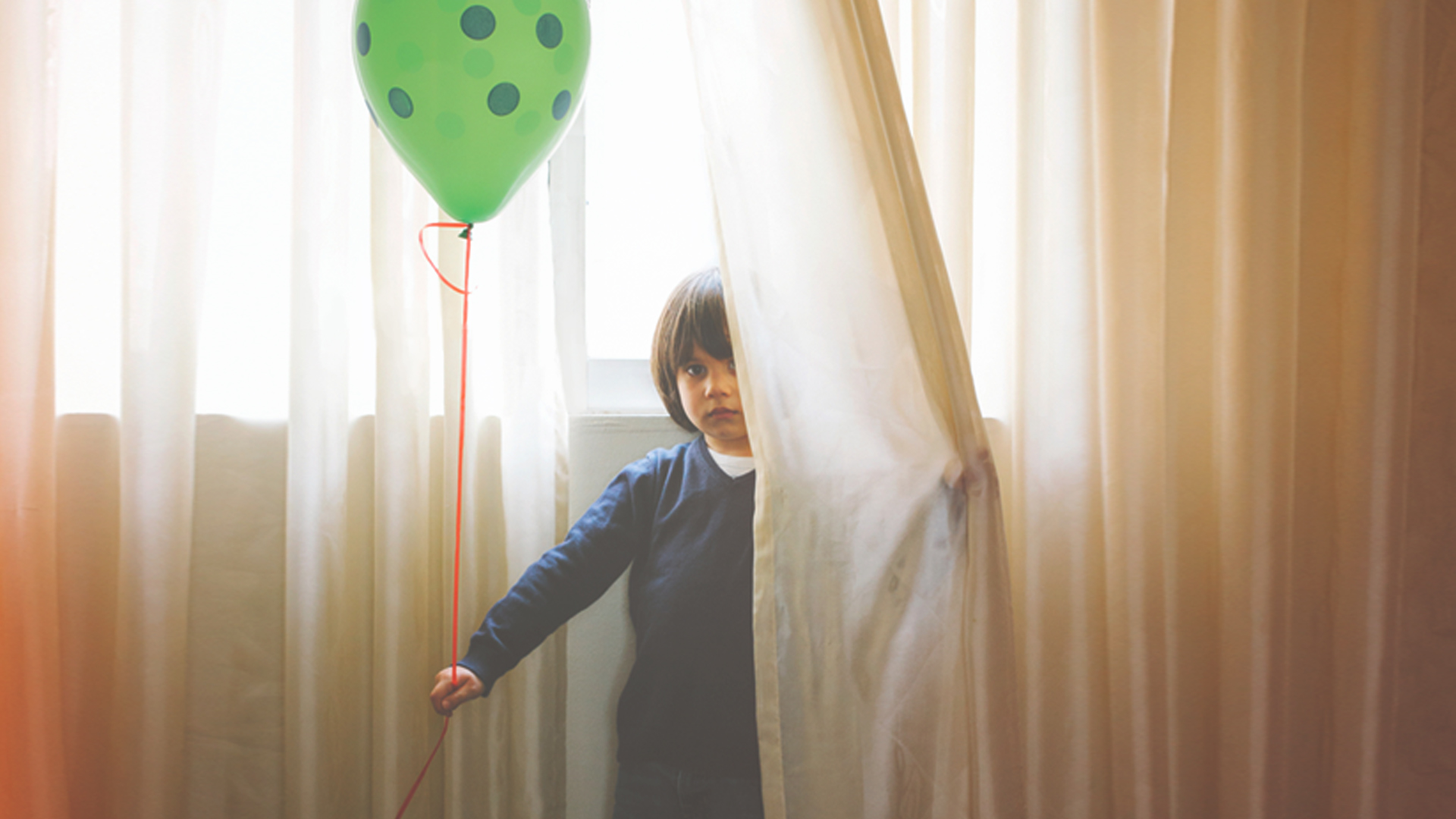Boy hiding behind curtain holding a balloon in his hand