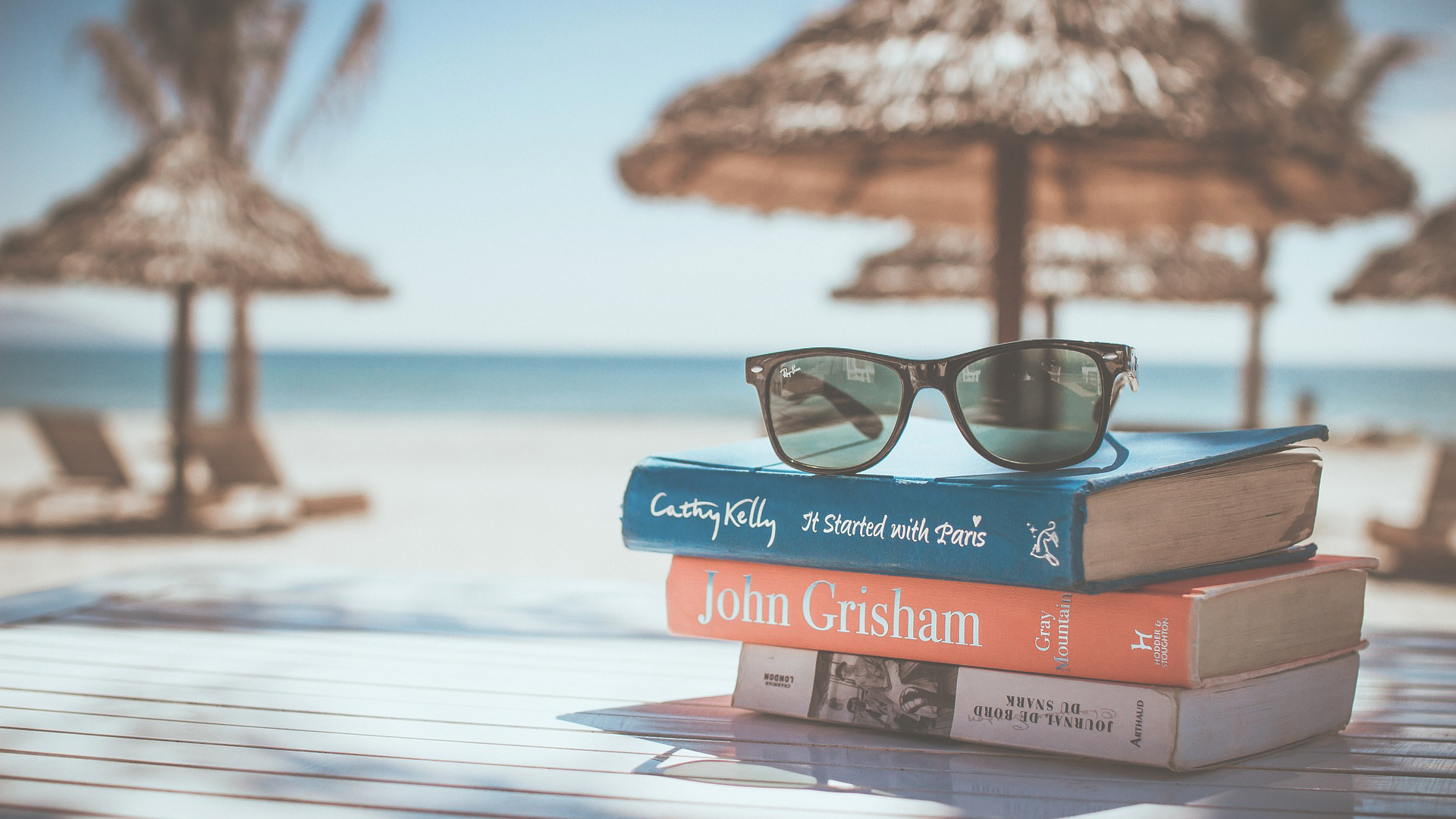 stack of books and glasses on a beach